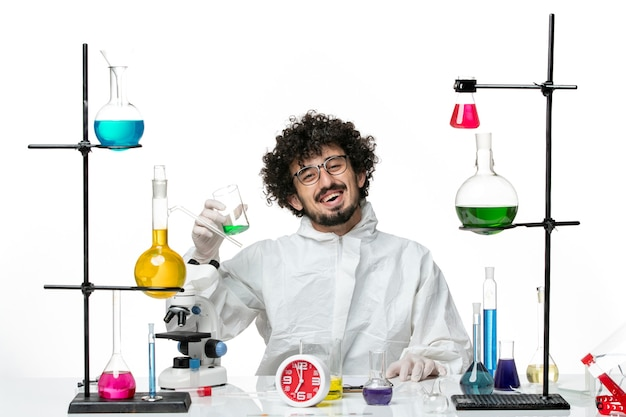 Front view young male scientist in special suit sitting with different solutions on a white wall