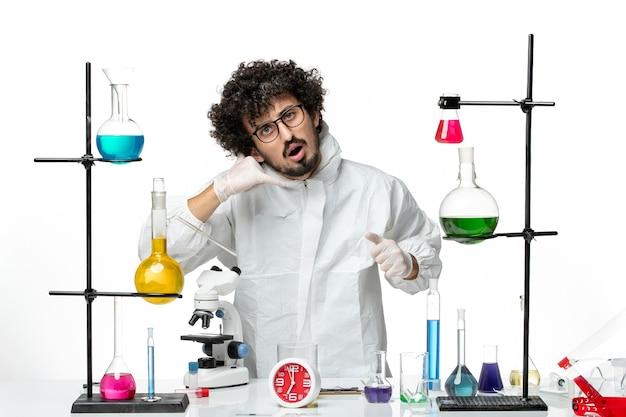 Vista frontale giovane scienziato maschio in abito speciale in piedi intorno al tavolo con soluzioni su un muro bianco chiaro science lab covid- chimica pandemica