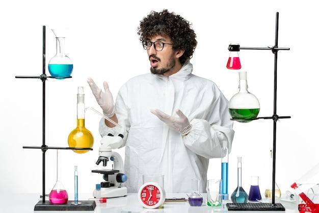 Vista frontale giovane scienziato maschio in abito speciale in piedi intorno al tavolo con soluzioni su un laboratorio scrivania bianca