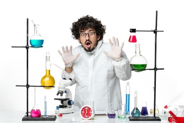 Giovane scienziato maschio di vista frontale in vestito speciale che sta intorno al tavolo con soluzioni sullo scrittorio bianco