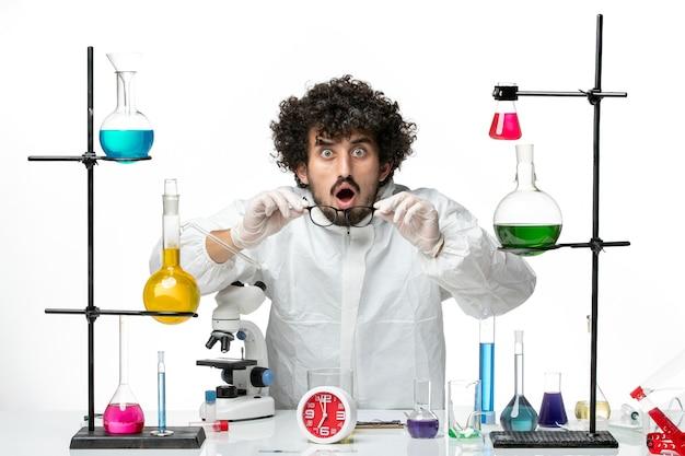 Giovane scienziato maschio di vista frontale in vestito speciale che sta intorno al tavolo con soluzioni sul laboratorio della parete bianca