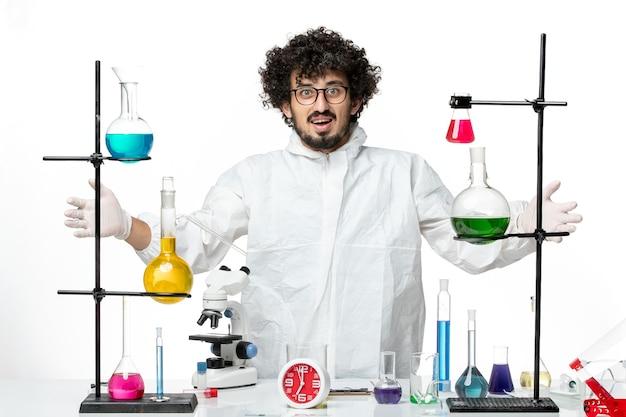 Giovane scienziato maschio di vista frontale in vestito speciale che sta intorno al tavolo con soluzioni sul muro bianco