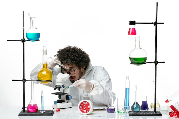 Front view young male scientist in special suit using microscope on the white wall