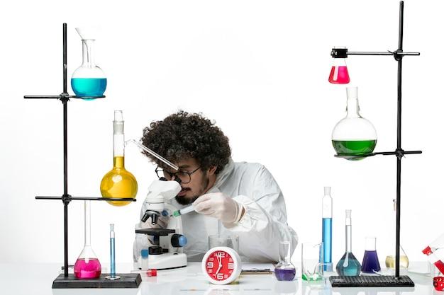 Giovane scienziato maschio di vista frontale in vestito speciale facendo uso del microscopio sulla parete bianca