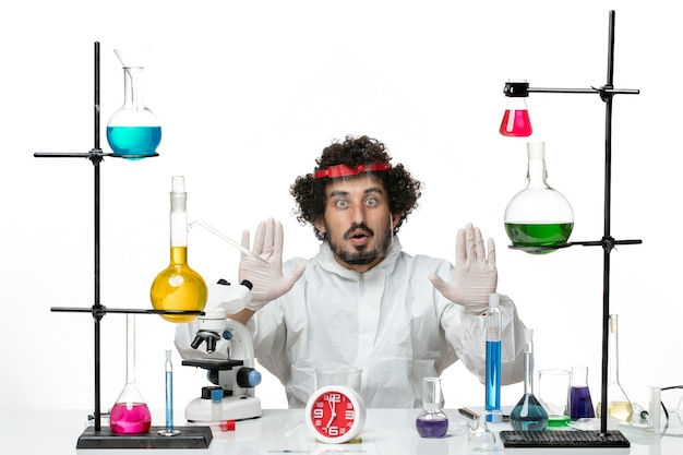 Front view young male scientist in special suit and wearing protective helmet