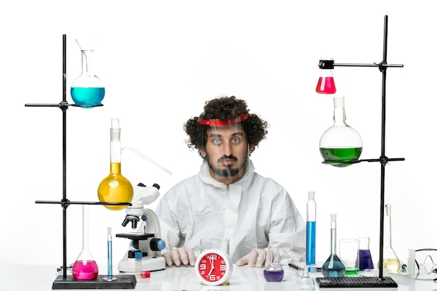 Front view young male scientist in special suit wearing special protective helmet on a white wall