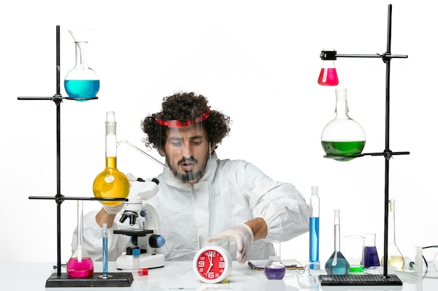 Front view young male scientist in special suit with protective helmet using microscope on light white wall