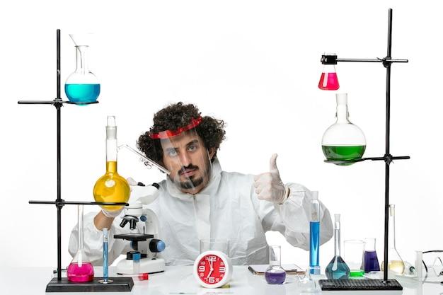 Giovane scienziato maschio di vista frontale in vestito speciale con il casco protettivo facendo uso del microscopio sul maschio di chimica covid del laboratorio di scienza della parete bianca