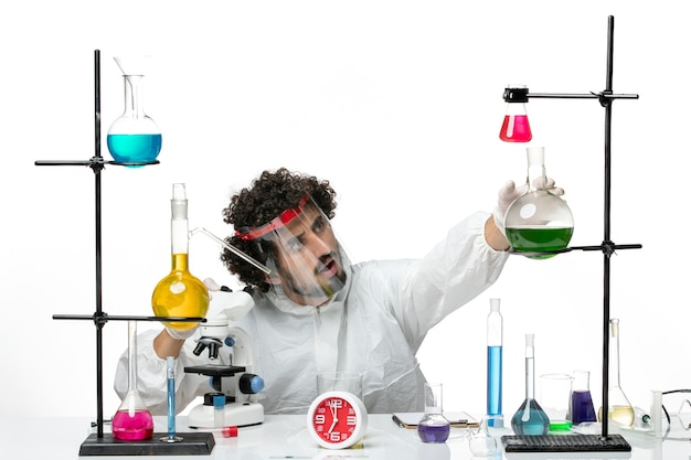 Front view young male scientist in special suit with protective helmet using microscope on white wall