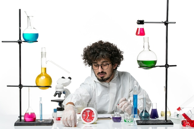 Front view young male scientist in special suit in working process on the white wall