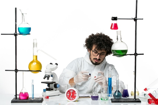 Front view young male scientist in special suit in working process on white wall