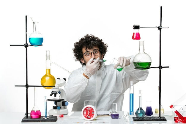 Front view young male scientist in special suit working with injection and solution on a white background