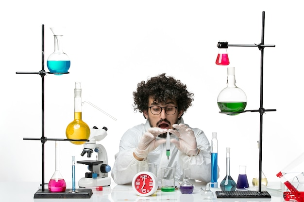 Front view young male scientist in special suit working with injection and solution on white wall