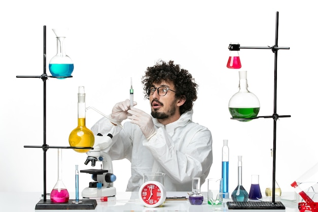 Front view young male scientist in special suit working with injection on white wall