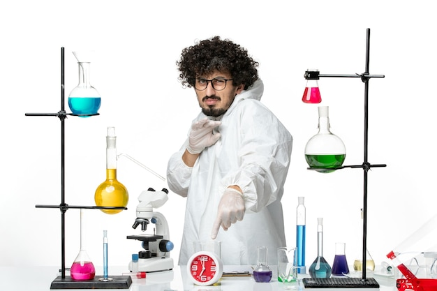 Front view young male scientist in white special suit inside room with solutions