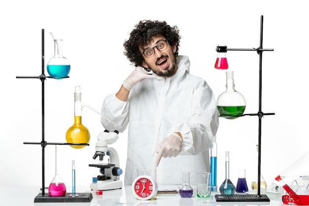 Giovane scienziato maschio di vista frontale in posa speciale bianca del vestito