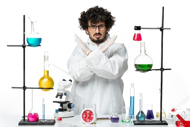 Front view young male scientist in white special suit showing ban sign on white wall science covid lab pandemic chemistry