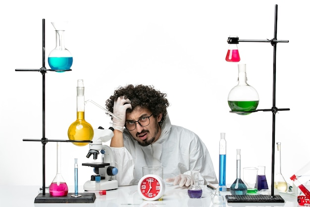Front view young male scientist in white special suit sitting with solutions