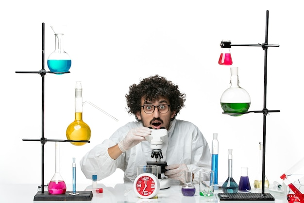 Front view young male scientist in white special suit trying to use microscope