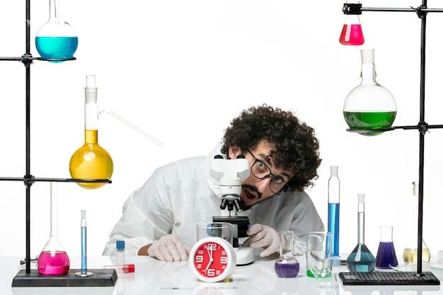 Giovane scienziato maschio di vista frontale in vestito speciale bianco che prova a usare il microscopio