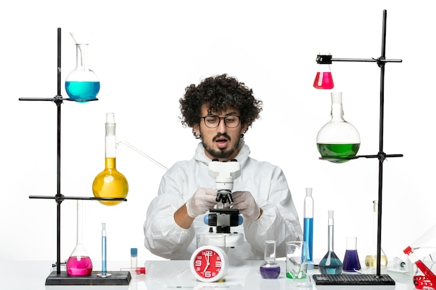 Front view young male scientist in white special suit using microscope