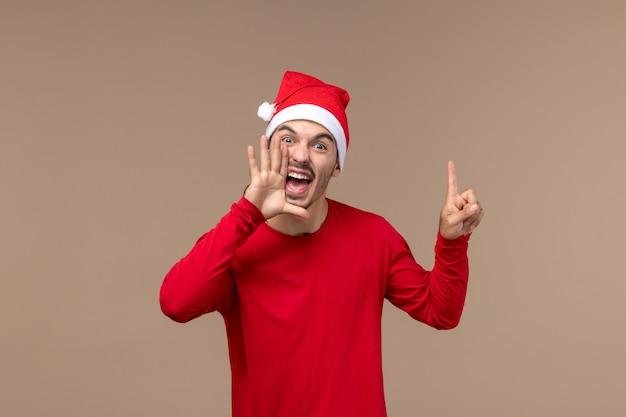 Вид спереди молодой самец кричит на коричневом фоне рождественские эмоции праздник самца