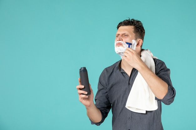 正面図青い背景にかみそりで顔を剃っている若い男性