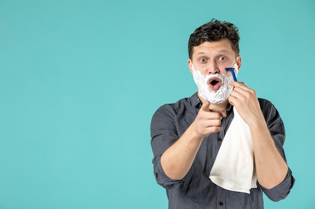 Front view young male shaving his foamed face with razor on blue background