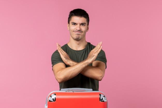 Giovane maschio di vista frontale che mostra il segno di divieto sullo spazio rosa