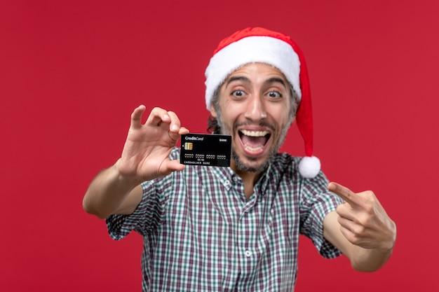 Вид спереди молодой мужчина показывает банковскую карту на красном фоне