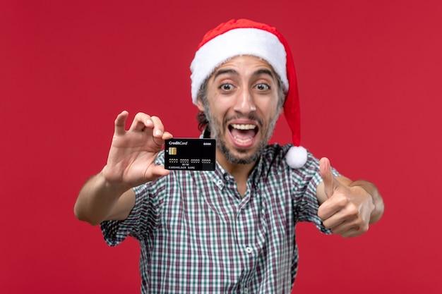 빨간 책상에 은행 카드를 보여주는 전면보기 젊은 남성