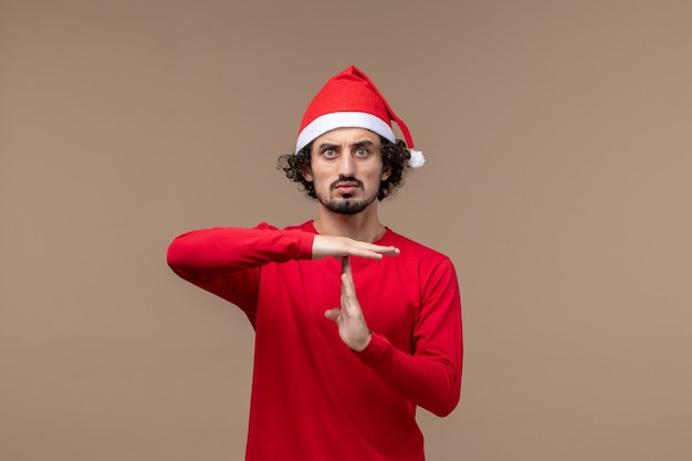 Front view young male showing t sign on brown background emotion christmas holiday