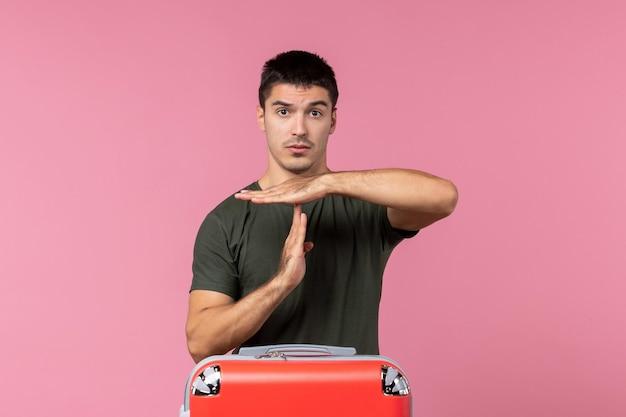 Vista frontale giovane maschio che mostra il segno t sullo spazio rosa