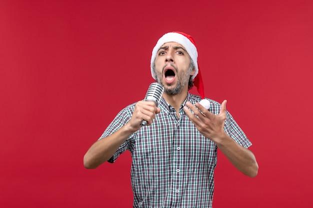Vista frontale giovane maschio cantando con microfono su sfondo rosso