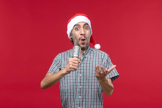 Giovane maschio di vista frontale che canta con il microfono sulla scrivania rossa