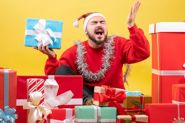 黄色の背景にクリスマスプレゼントの周りに座っている正面図若い男性