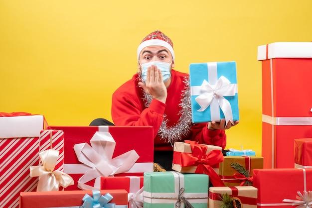 Вид спереди молодой мужчина сидит вокруг рождественских подарков на желтом фоне