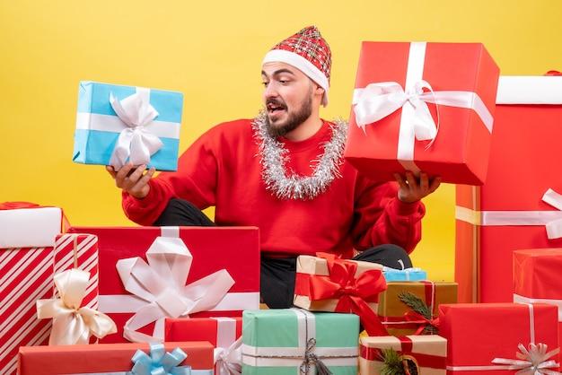 크리스마스 주위에 앉아 전면보기 젊은 남성 노란색 배경에 선물