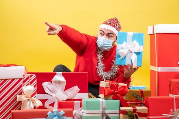 黄色の背景にクリスマスプレゼントの周りに座っている正面図若い男性 無料写真