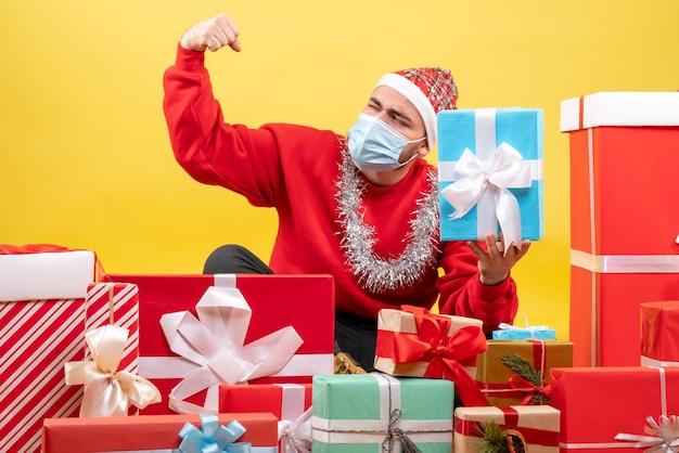 Вид спереди молодого мужчины, сидящего вокруг рождественских подарков на желтом