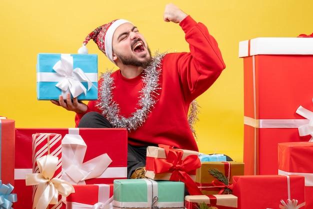 正面図黄色の背景に喜んでクリスマスプレゼントの周りに座っている若い男性