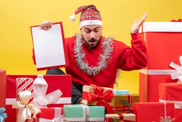 Вид спереди молодого мужчины, сидящего вокруг рождественских подарков с запиской на желтом фоне