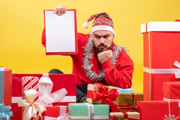 Front view young male sitting around christmas presents with note on yellow background
