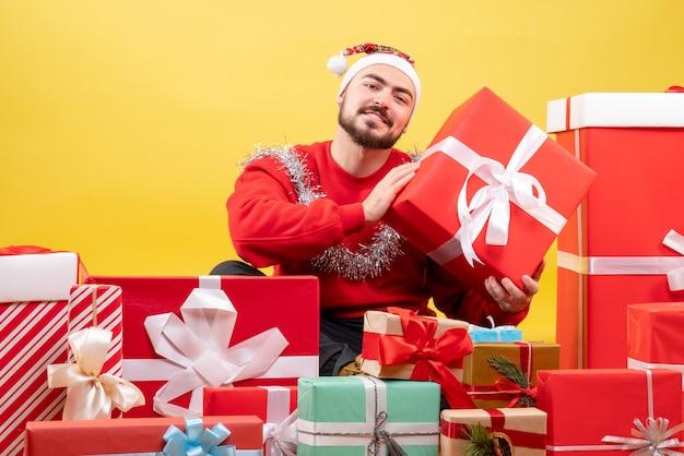 Giovane maschio di vista frontale che si siede intorno ai regali di natale su fondo giallo