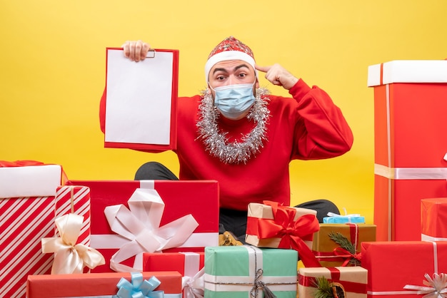 Front view young male sitting around christmas presents on yellow background