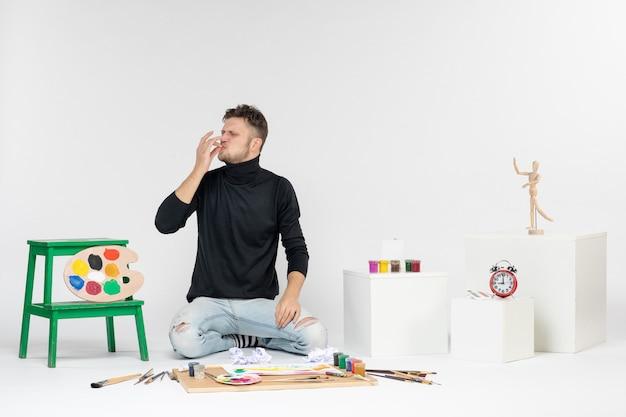 白い壁に描くための絵の具やタッセルの周りに座っている正面図の若い男性は、カラー絵の絵を描くアーティストのペイントアートを描く