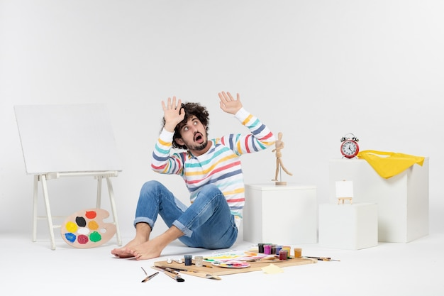 Front view of young male sitting around paints and drawings on a white wall