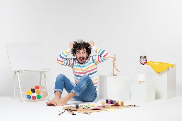 Vista frontale del giovane maschio seduto intorno a pitture e disegni su muro bianco