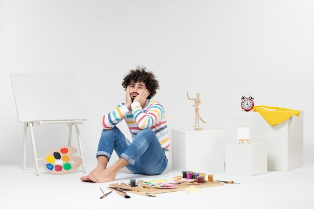 Front view of young male sitting around paints and drawings on white wall