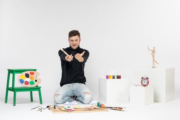 白い壁に描くためのタッセルを保持している絵の具の周りに座っている正面図若い男性は絵を描く絵の色アーティストの絵の具を描く
